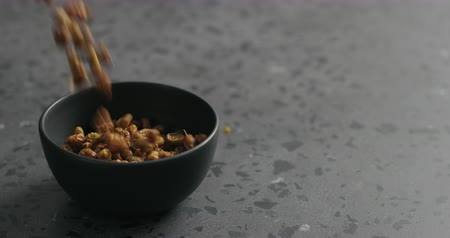 buckthorn : Slow motion dried seaberry falling into black bowl on terrazzo countertop Stock Footage