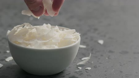 shred : Slow motion man hand takes coconut chips from white bowl on terrazzo surface Stock Footage