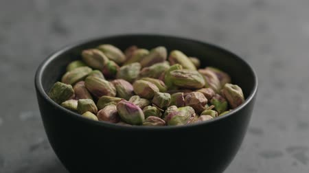 pistache : Slow motion man hand takes pistachio kernels from black bowl on terrazzo surface Stock Footage