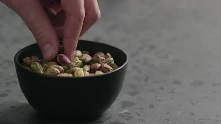 soyulmuş : Slow motion man hand takes pistachio kernels from black bowl on terrazzo surface Stok Video
