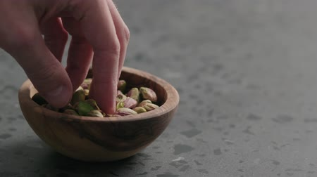 pistacje : Slow motion man hand takes pistachio kernels from olive bowl on terrazzo surface