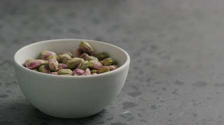 soyulmuş : Slow motion man hand takes pistachio kernels from white bowl on terrazzo surface Stok Video