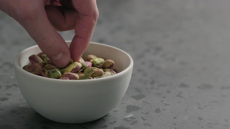 kurutulmuş : Slow motion man hand takes pistachio kernels from white bowl on terrazzo surface Stok Video