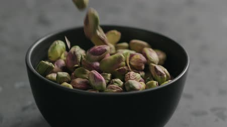 pistacje : Slow motion peeled pistachios falls into black bowl on terrazzo surface Wideo