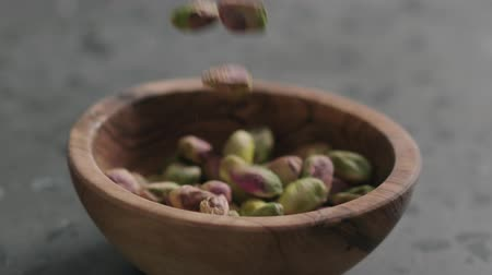pistache : Slow motion peeled pistachios falls into olive bowl on terrazzo surface