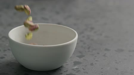 soyulmuş : Slow motion peeled pistachios falls into white bowl on terrazzo surface Stok Video