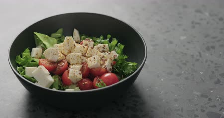 len : Slow motion handheld shot of salad with mozzarella, cherry tomatoes and frisee leaves in black bowl on terrazzo surface Stock mozgókép