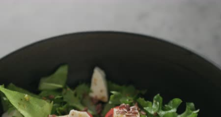 espinafre : Slow motion handheld shot of salad with mozzarella, cherry tomatoes and frisee leaves in black bowl on terrazzo surface Stock Footage