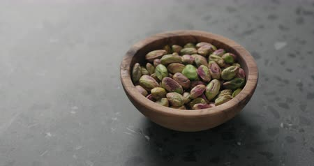 pistacje : Handheld slow motion peeled pistachios in olive bowl on terrazzo surface Wideo