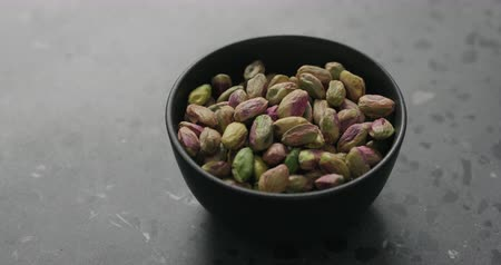 soyulmuş : Handheld slow motion peeled pistachios in black bowl on terrazzo surface Stok Video