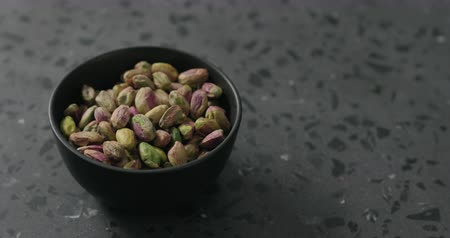 pistacje : Handheld slow motion peeled pistachios in black bowl on terrazzo surface Wideo