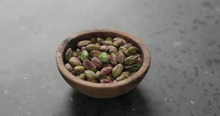 olivy : Handheld slow motion peeled pistachios in olive bowl on terrazzo surface Dostupné videozáznamy