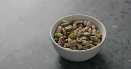 pistacje : Handheld slow motion peeled pistachios in white bowl on terrazzo surface