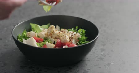 szpinak : Slow motion closeup man hand pick salad with mozzarella, cherry tomatoes and frisee leaves in black bowl on terrazzo surface Wideo