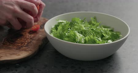 szpinak : Slow motion man hands preparing salad with mozzarella, cherry tomatoes and frisee leaves in white bowl on terrazzo surface