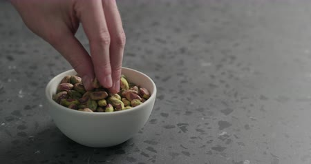 pistacje : Slow motion man hand takes pistachio kernels from white bowl on terrazzo surface Wideo