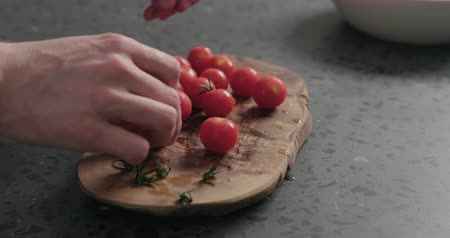 tomates cereja : Slow motion man hands remove stems from cherry tomatoes on olive board