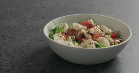 szpinak : Slow motion closeup man hand pick salad with mozzarella, cherry tomatoes and frisee leaves in white bowl on terrazzo surface