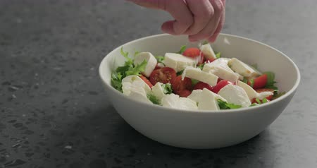 espinafre : Slow motion man hands salting salad with mozzarella, cherry tomatoes and frisee leaves in white bowl on terrazzo surface