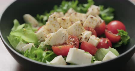 len : rotating shot of salad with mozzarella, cherry tomatoes and frisee leaves in black bowl