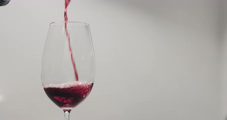 bordeaux : Slow motion pour red wine into wine glass from bottle with copy space