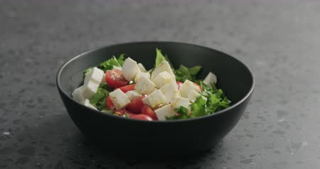 len : Slow motion man hands ground spices to salad with mozzarella, cherry tomatoes and frisee leaves in black bowl on terrazzo surface Stock mozgókép