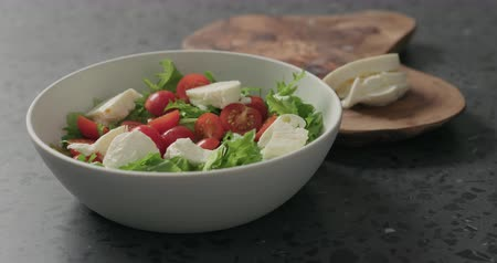 mozzarelle : Slow motion man hands preparing salad with mozzarella, cherry tomatoes and frisee leaves in white bowl on terrazzo surface
