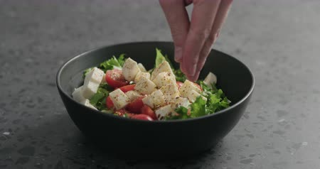 len : Slow motion man hands add flaxseed to salad with mozzarella, cherry tomatoes and frisee leaves in black bowl on terrazzo surface