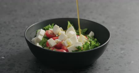 len : Slow motion man hands add olive oil to salad with mozzarella, cherry tomatoes and frisee leaves in black bowl on terrazzo surface