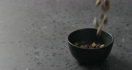 pistacchi : Slow motion peeled pistachios falls into black bowl on terrazzo surface Filmati Stock