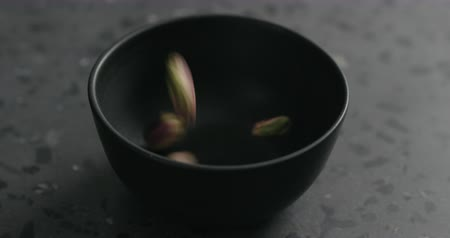 soyulmuş : Slow motion peeled pistachios falls into black bowl on terrazzo surface Stok Video