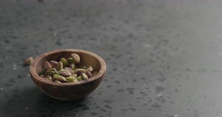 очищенные : Slow motion peeled pistachios falls into olive bowl on terrazzo surface