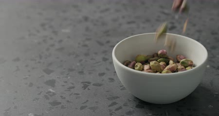 pistacje : Slow motion peeled pistachios falls into white bowl on terrazzo surface Wideo