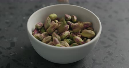 pistache : Slow motion peeled pistachios falls into white bowl on terrazzo surface Stockvideo
