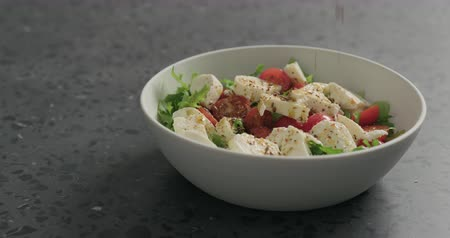 len : Slow motion man hands add flaxseed to salad with mozzarella, cherry tomatoes and frisee leaves in white bowl on terrazzo surface