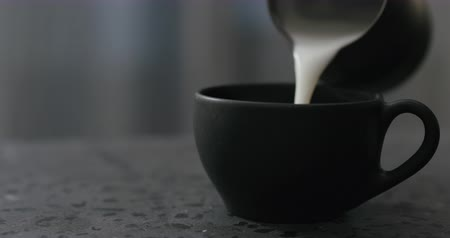 jarro : Slow motion pouring steamed milk into cappuccino in black cup on terrazzo countertop