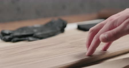 nogueira : Slow motion man hand cleans black walnut board before applying finish