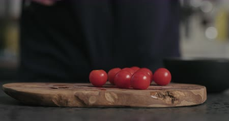 olive wood : Slow motion man cut cherry tomatoes on olive wood board