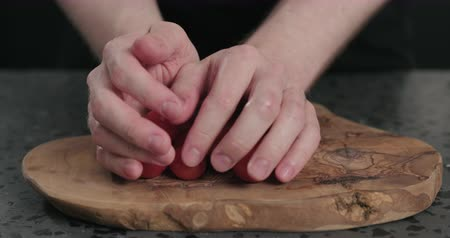 tomate cereja : Slow motion man put cherry tomatoes on olive wood board