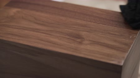 black walnut : woodworker applying oil finish to black walnut storage box Stock Footage