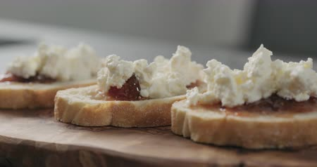 fig : Slow motion handheld shot of bruschetta with ricotta and fig marmalade on olive board Stock Footage