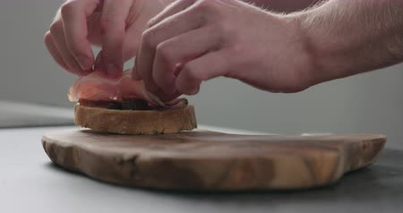 przekąski : Slow motion man add pancetta to slice of ciabatta with fig marmalade Wideo