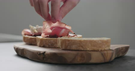 bruschetta : Slow motion man add pancetta to slice of ciabatta with fig marmalade Stock Footage