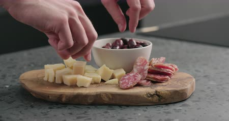 olivy : Slow motion man hand takes olives, cheese and fuet from olive wood board
