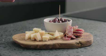 antipasti : Slow motion man hand takes olives, cheese and fuet from olive wood board