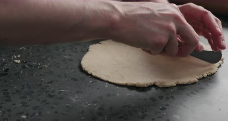 grissini : Slow motion man cutting flat dough with knife Stock Footage