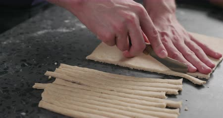 grissini : Slow motion man slicing flat dough with knife for making grissini