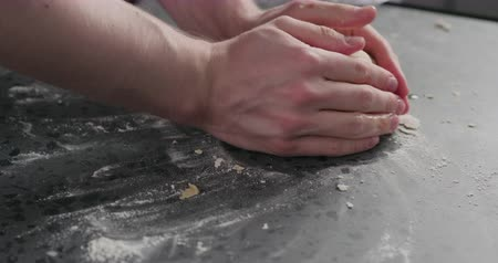 grissini : Slow motion man pack dough into plastic back for resting on concrete countertop