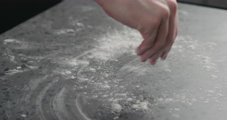 countertop : Slow motion man sprinkles flour on countertop