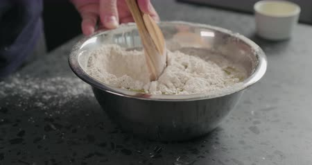 grissini : Slow motion man mixing wet ingredients into flour in steel bowl on concrete countertop